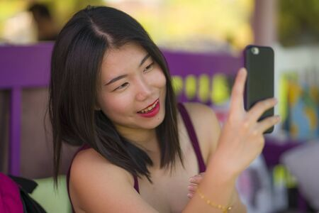 sweet Asian girl taking selfie with hand phone . young beautiful and happy Korean woman taking self portrait photo smiling cheerful sitting outdoors enjoying Summer holidays