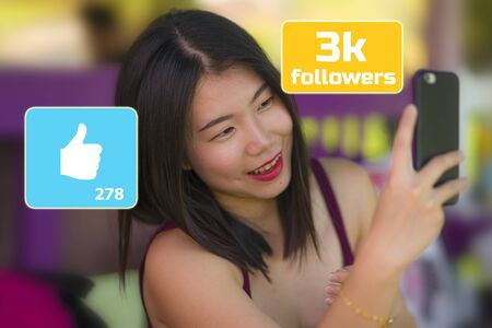 natural lifestyle portrait of young sweet and happy Asian Korean girl taking selfie photo with hand phone outdoors composed with social media app likes and online followers icons as internet blogger