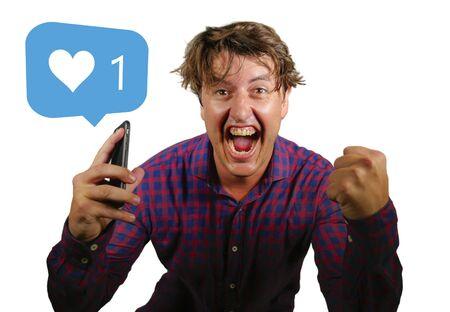 Dipendenza e ossessione dai social media. divertente ritratto di giovane pazzo felice ed eccitato che celebra un singolo online come su internet app guardando il suo telefono cellulare isolato su sfondo bianco