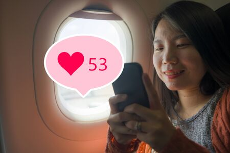Asian girl sharing travel experience on social media . young happy and beautiful Korean tourist woman in airplane cabin receiving internet likes while online posting her holiday trip