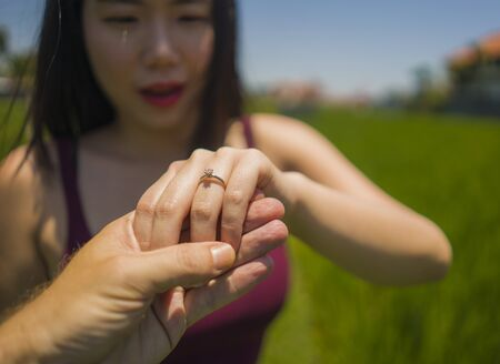 Romantic marriage proposal . close up hands of happy Asian couple in love holding together , the woman with engagement ring on her finger isolated on green field background