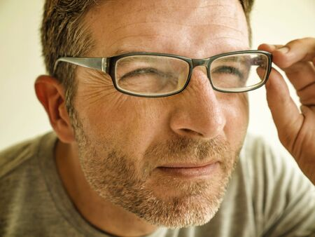 close up face portrait of man checking vision trying glasses at optometrist . guy 40s during optical examination testing spectacles correcting myopia struggling suffering blurred eyesight problem