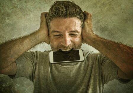 dramatic portrait of sick and crazy stressed man biting mobile phone screaming desperate and hysteric looking like a weirdo in life problem and stress concept isolated on grunge background
