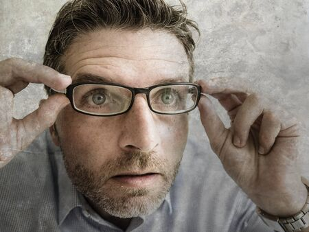 close up face portrait of man wearing glasses in shock and surprise face expression. guy opening eyes wide looking or reading something amazing or surprising in disbelief Stock fotó
