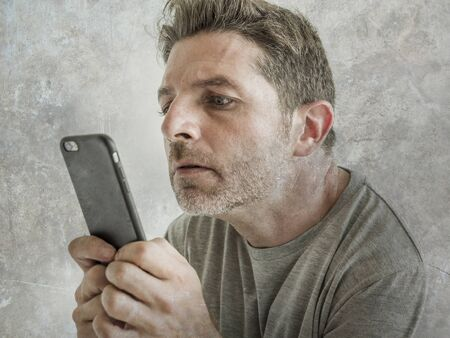 freak and weird looking man using mobile phone watching something online in sick intense face expression in internet and social media addiction concept isolated on grunge background