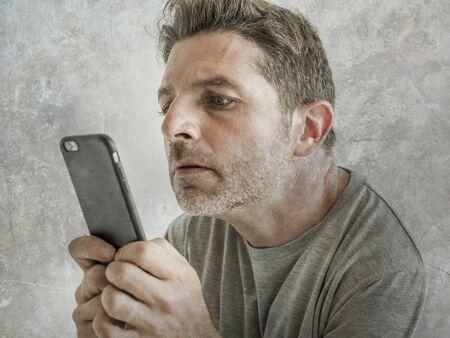 homme étrange et bizarre utilisant un téléphone portable en regardant quelque chose en ligne dans une expression de visage intense malade dans le concept de dépendance à Internet et aux médias sociaux isolé sur fond grunge