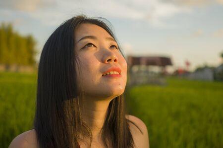 junge glückliche und schöne asiatische Frau, die die Natur am Reisfeld genießt. süßes chinesisches Mädchen im Sommerkleid auf der grünen Wiese, das die Landschaft während der Urlaubsreise in Fernweh und Tourismus erkundet