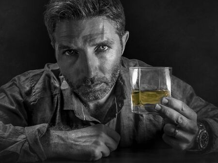 dramatic portrait of depressed and thoughtful alcoholic man on his 40s in front of whiskey glass wasted and stressed holding on temptation to drink in alcohol addiction and alcoholism problem