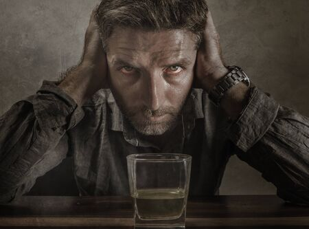 Attractive desperate alcoholic man . depressed addict isolated in front of whiskey glass trying not drinking in dramatic expression suffering alcoholism and alcohol addiction problem 写真素材 - 132088378