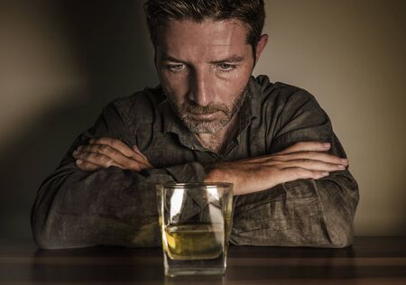 Attractive desperate alcoholic man . depressed addict isolated in front of whiskey glass trying not drinking in dramatic expression suffering alcoholism and alcohol addiction problem 写真素材 - 132088381