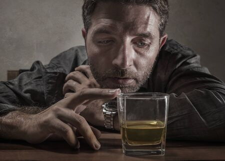 Attractive desperate alcoholic man . depressed addict isolated in front of whiskey glass trying not drinking in dramatic expression suffering alcoholism and alcohol addiction problem