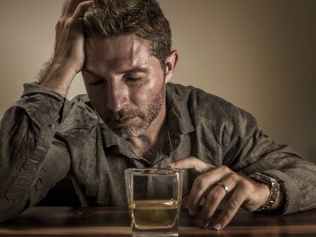 Attractive desperate alcoholic man . depressed addict isolated in front of whiskey glass drunk and wasted in dramatic expression suffering alcoholism and alcohol addiction problem