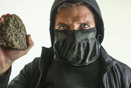 young man as radical and aggressive anarchist rioter holding brick threatening. furious anti-system protester in face mask throwing stone in violent riot isolated on white background