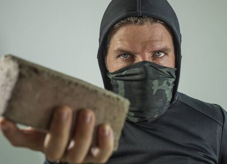 young man as radical and aggressive anarchist rioter holding brick threatening. furious anti-system protester in face mask throwing stone in violent riot  isolated on white background Banco de Imagens