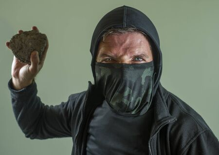 young man as fanatic and aggressive anarchist rioter . furious and scary violent anti-system protester in face mask throwing stone looking hostile at fighting riot in radical demonstration Imagens