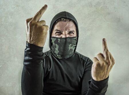 joven como alborotador anarquista fanático y agresivo que da el dedo medio. Manifestante antisistema violento furioso y aterrador en mascarilla gritando hostil en la lucha contra disturbios en manifestación radical