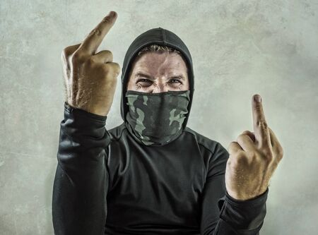 young man as fanatic and aggressive anarchist rioter giving middle finger. furious and scary violent anti-system protester in face mask screaming hostile at fighting riot in radical demonstration Imagens