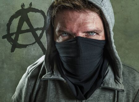 young man as violent and ultra anarchist rioter . furious anti-system protester in face mask hostile at fighting riot in radical demonstration isolated on grey with anarchy symbol background
