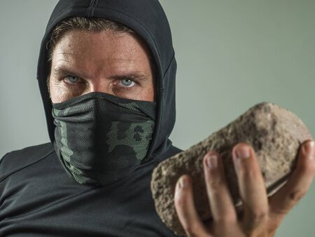 young man as radical and aggressive anarchist rioter holding brick threatening. furious anti-system protester in face mask throwing stone in violent riot  isolated on white background Imagens