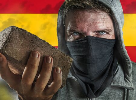 young man as ultra and extremist Spanish nationalism defender. violent protester in face mask holding a brick at fighting riot in radical demonstration isolated on Spain flag background