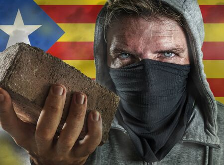 young Catalan man as ultra and radical separatist holding brick protesting in face mask holding brick threatening at nationalistic riot isolated on Catalonia independentist flag background Imagens