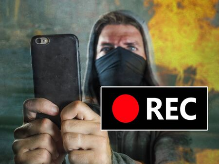 young rioter filming street chaos . ultra and radical man masked recording riot video on mobile phone during violent turmoil witnessing brutality at anti system demonstration