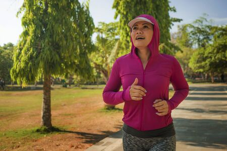 attractive middle aged lady running happy at city park . beautiful and sporty woman on her 40s exercising doing jogging workout on a sunny morning enjoying healthy lifestyle and fitness