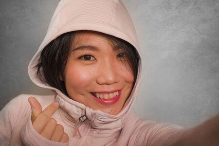 Jeune belle et heureuse étudiante coréenne asiatique prenant une photo de portrait de selfie pour utiliser l'application de médias sociaux en profitant d'un sourire ludique faisant des gestes doux dans une capuche de style hipster sur fond isolé