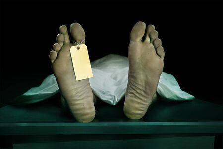 Male human body lying dead at morgue with blank identity label and covered with sheet . Close-up foot of man cadaver with identification toe tag in human life loss and death concept isolated on black