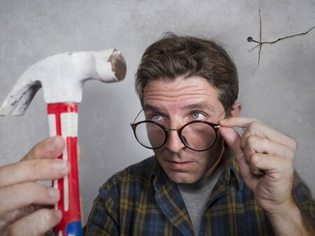 portrait of nerd man looking to hammer after driving a nail for hanging a frame making funny face for the  mess cracking the wall as a disaster DIY guy and messy domestic repair task at home Banco de Imagens