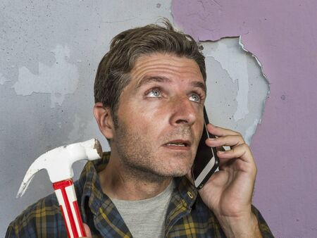 funny portrait of messy and frustrated man calling domestic insurance on mobile phone for repair mess he did with a hammer cracking the wall needing professional help of repairman