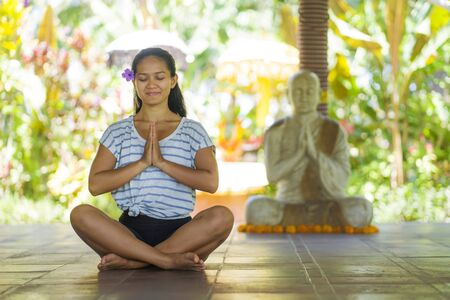 young beautiful and happy Asian Indonesian woman with Balinese style ear flower sitting on wood floor in lotus pose meditating with eyes closed at yoga studio relaxed in harmony concept