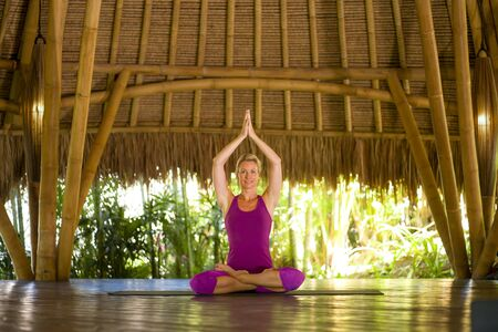 young happy and beautiful blond American woman doing yoga workout in Bali at exotic bamboo hut opened to forest view sitting in lotus pose meditating enjoying retreat in balance and harmony
