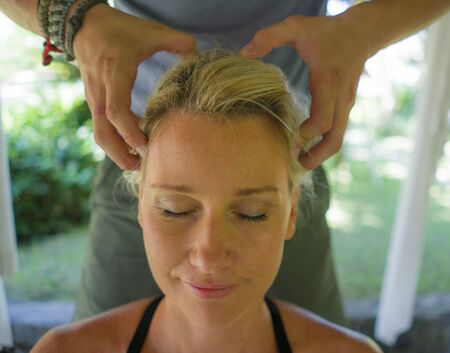Closeup masseur hands and face of young beautiful and happy American tourist woman having traditional massage at Asian outdoors spa enjoying holidays retreat and healthy lifestyle