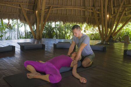 young beautiful and happy American tourist woman having traditional Thai massage in her body by Asian masseur at  outdoors hut enjoying holidays retreat and natural healthy lifestyle