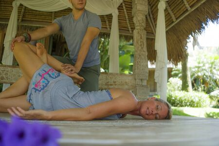 young beautiful and happy American tourist woman having traditional Thai massage in her body by Asian masseur at  outdoors spa enjoying holidays retreat and healthy lifestyle