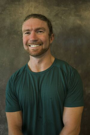 good vibes portrait of young happy and attractive red hair American man in cool hipster style smiling confident and positive as fitness personal trainer isolated on grunge studio background