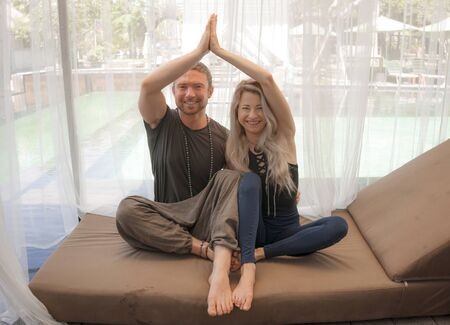 holiday yoga retreat portrait of young happy and beautiful hipster couple sitting in lotus position together enjoying zen lifestyle smiling cheerful and relaxed in wellness balance and harmony Stock Photo