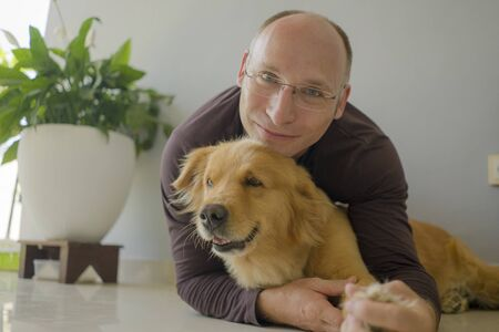 natural lifestyle portrait of young happy and cheerful man at home playing with his dog, a beautiful retriever, the guy smiling sweet cuddling the pet in connection and bonding concept Zdjęcie Seryjne - 133814762