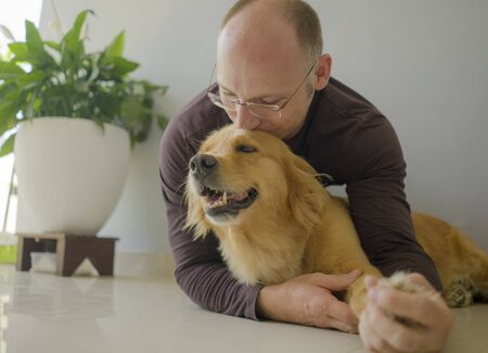 natural lifestyle portrait of young happy and cheerful man at home playing with his dog, a beautiful retriever, the guy smiling sweet cuddling the pet in connection and bonding concept