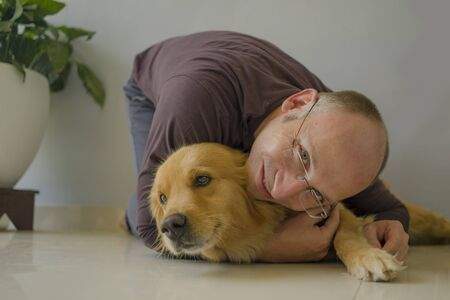 natural lifestyle portrait of young happy and cheerful man at home playing with his dog, a beautiful retriever, the guy smiling sweet cuddling the pet in connection and bonding concept Zdjęcie Seryjne - 133814768