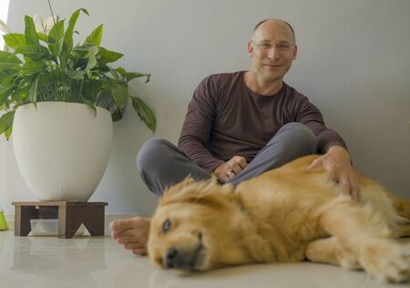 natural lifestyle portrait of young happy and cheerful man at home playing with his dog, a beautiful retriever, the guy smiling sweet cuddling the pet in connection and bonding concept Zdjęcie Seryjne - 133814770