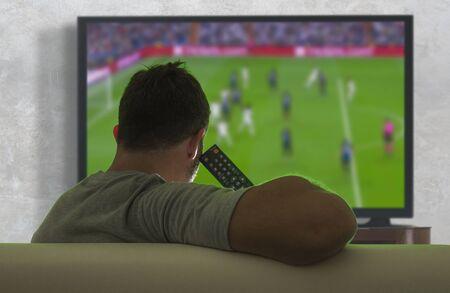 Blick von hinten auf einen jungen Fußballfan, der ein europäisches Fußballspiel auf einem Großbildfernseher auf der Sofacouch im Wohnzimmer sieht und die Emotionen, die sein Team anfeuern, genießt und fühlt