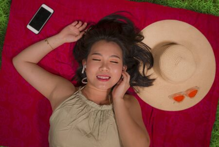 outdoors lifestyle portrait of young happy and beautiful Asian Korean student girl chilling on city park relaxed listening to music with earpiece lying flat on sarong over green grass delighted 版權商用圖片