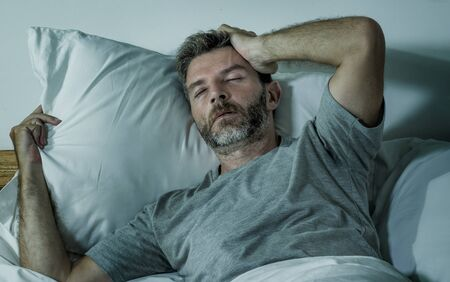 dramatic lifestyle portrait of young sad and depressed man lying thoughtful and pensive on bed looking away feeling lost thinking suffering some problem in sadness emotion and depression concept Stok Fotoğraf