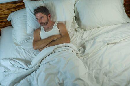 Dramatisches Lifestyle-Porträt eines jungen attraktiven traurigen und depressiven Mannes, der auf dem Bett liegt und nachts wach denkt und sich gestresst fühlt, Depressionsproblem in Traurigkeit und Melancholie-Konzept zu leiden Standard-Bild