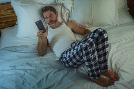 domestic lifestyle high angle portrait of young attractive and relaxed man at home lying on bed wearing pajamas using mobile phone networking and looking social media enjoying online time