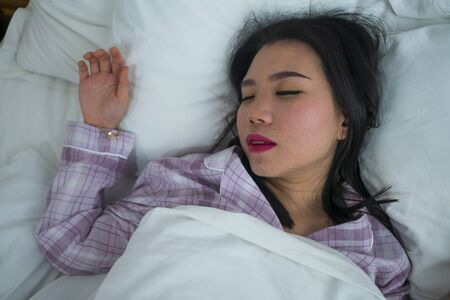 lifestyle portrait of young beautiful and sweet Asian Korean girl on her 20s alone at home sleeping relaxed wearing pajamas lying on bed happy and comfortable resting and dreaming
