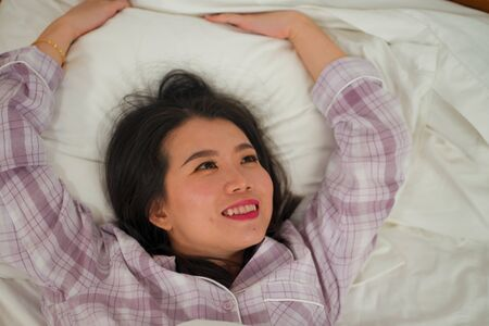 lifestyle portrait of young beautiful and sweet Asian Korean woman in bed feeling happy and relaxed wearing cute pajamas enjoying lazy Sunday morning at home playing cozy