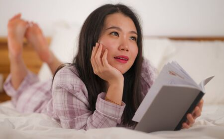 lifestyle portrait of young beautiful and sweet Asian Chinese woman in bed reading book novel feeling happy and relaxed or studying at home wearing cute pajamas looking cozy and homey